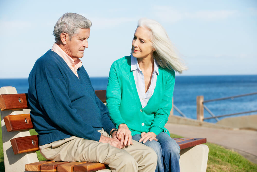 Altes Paar auf Bank am Meer