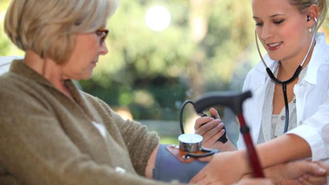 Ärztin misst Blutdruck bei alter Frau