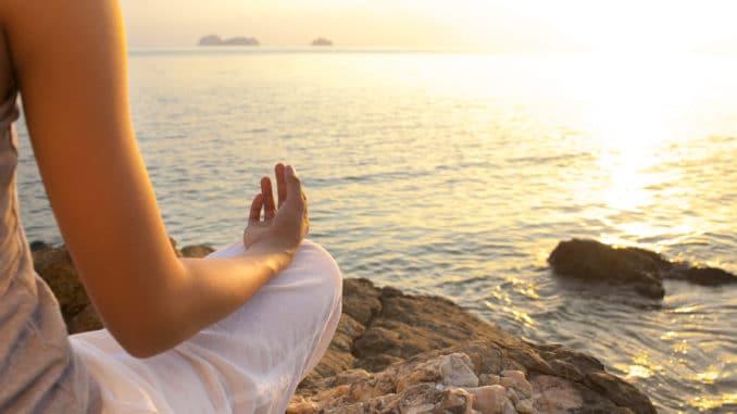 Frau meditiert am Strand