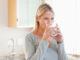 Frau trinkt Wasser in der Küche