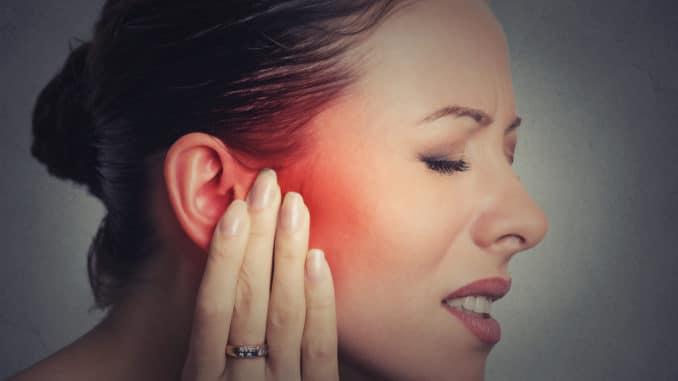 Junge Frau mit schlimmem Tinnitus